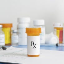 Prescription bottle on patient chart with medication bottles and supplies in background.