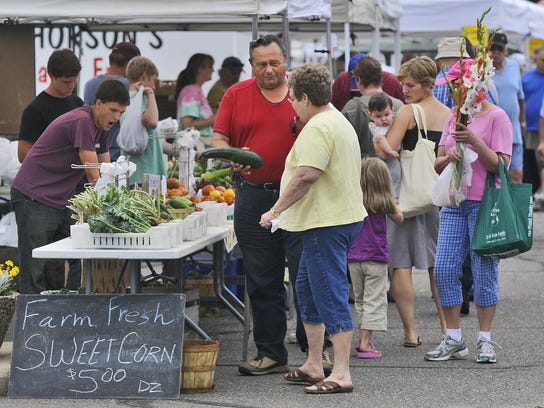Customers peruse the vegetables, flowers and other items available during the St. Cloud Area Farmers Market.