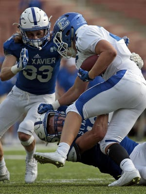 Covington Catholic running back Grant Dyer is brought down on a carry during the first quarter of a Crosstown Showdown game between St. Xavier and Covington Catholic at Nippert Stadium Aug. 28. St. Xavier allowed one touchdown in its 57-7 win.