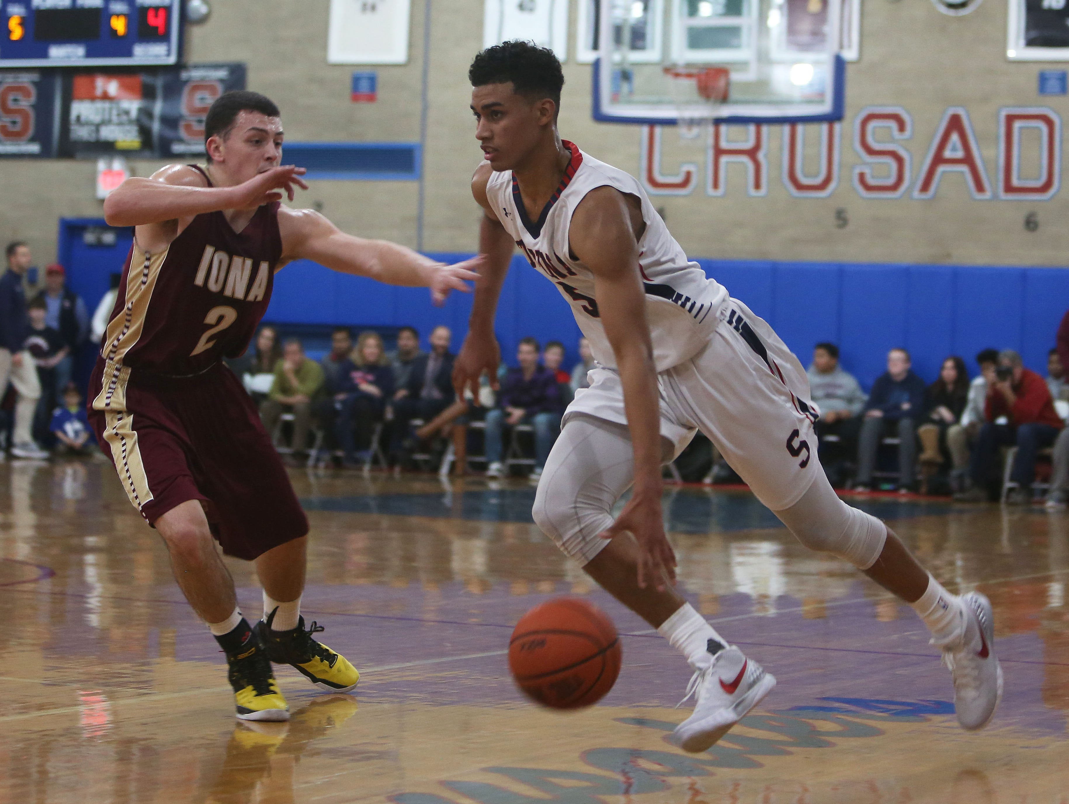 Stepinac's Jordan Tucker (5) drives to the basket while covered by Iona's Jon Brennen (2) during boys basketball action at Archbishop Stepinac High School in White Plains Jan. 8, 2016.