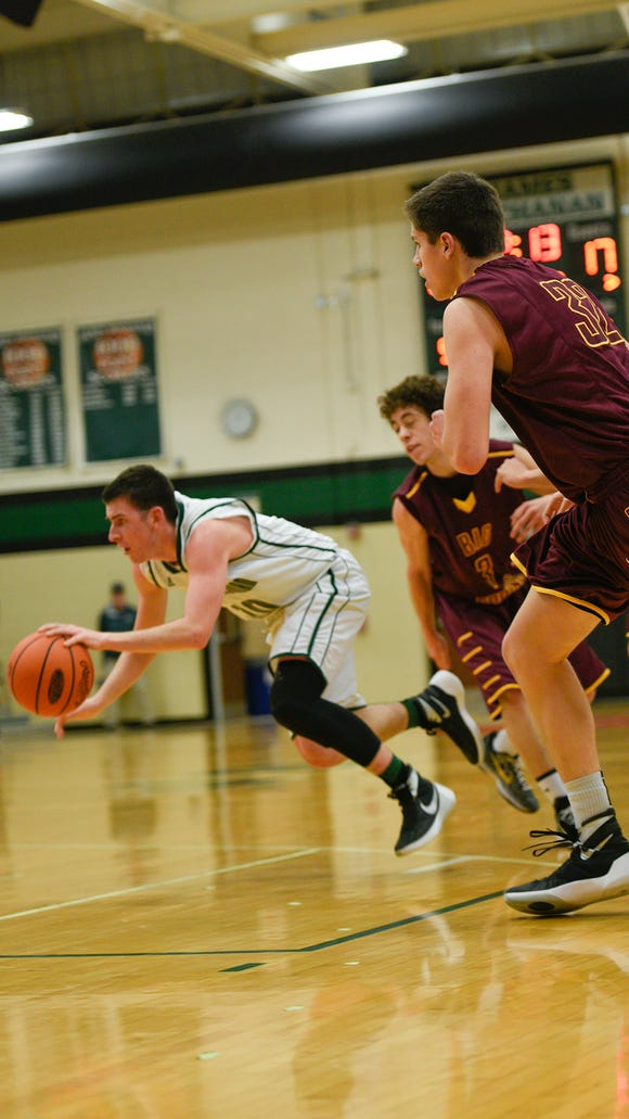 James Buchanan's Jared Pine (2) tries to keep his balance holding the ball as Ryker Armond (3) and Josh Header (32) of Big Spring try to catch up with him to defend during a boys basket ball game on Tuesday, Jan. 12, 2015 in Mercersburg, Pa. James Buchanan beat Big Spring 75-48.