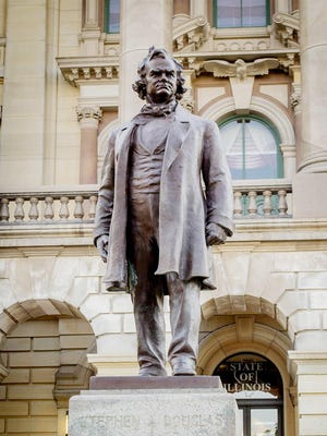A statue of Stephen Douglas sits directly behind one of his political rival Abraham Lincoln at the Illinois Statehouse. House Speaker Michael Madigan on Thursday called for a removal of Douglas' image from the Capitol grounds.