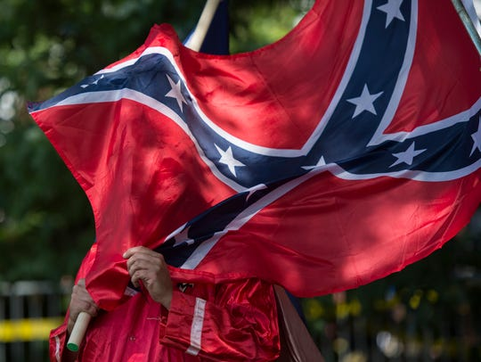 A member of the Ku Klux Klan holds a Confederate flag