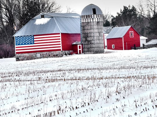 Fresh-fallen snow surrounds brightly painted farm buildings near St. John's University in this March 2018 file photo.