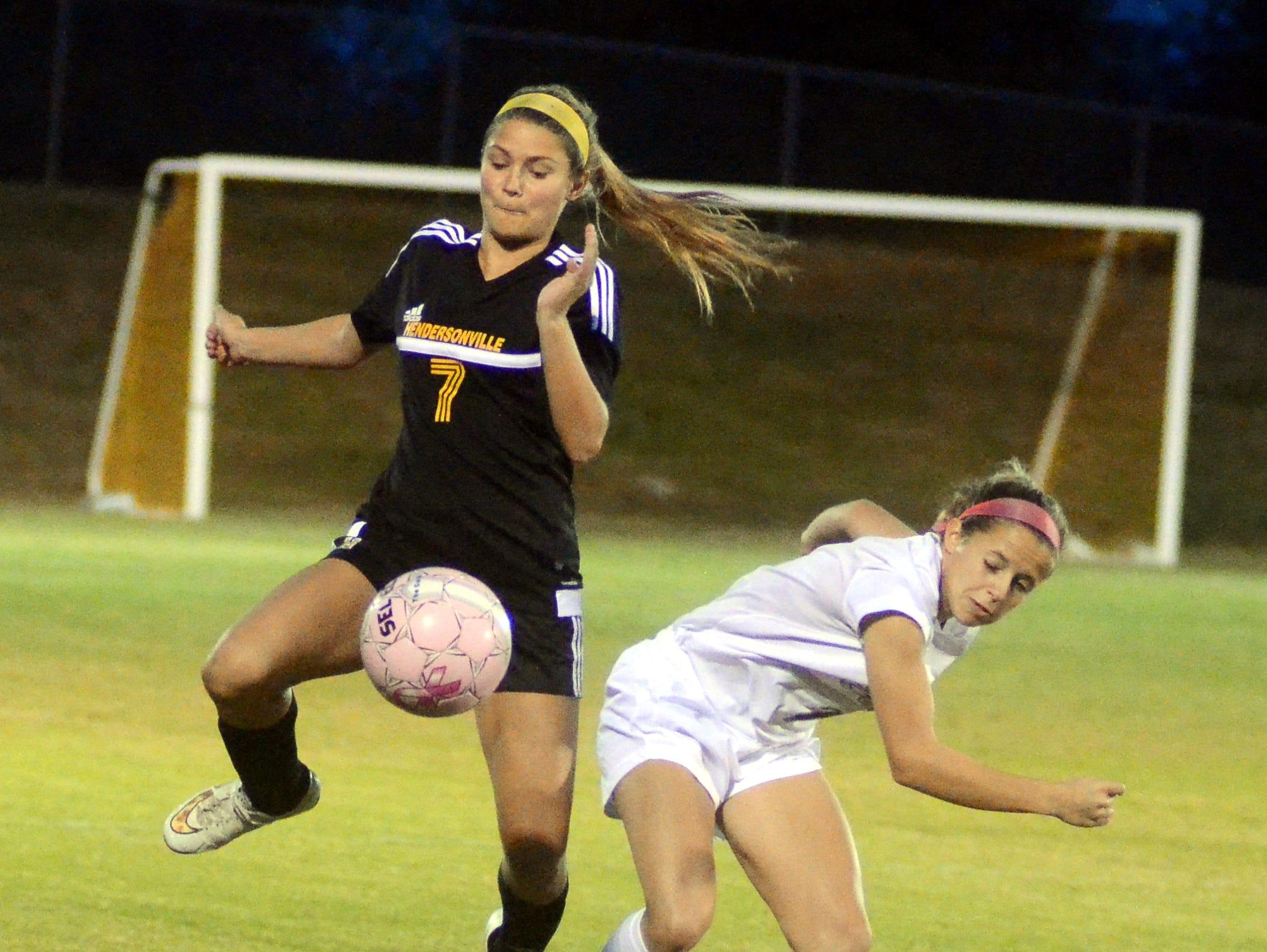 Hendersonville High junior Arden Butler battles with Independence junior Julie Garst for possession during first-half action.