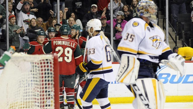 Wild players celebrate a goal by center Mikael Granlund (64) against Predators goalie Pekka Rinne (35) in the second period Saturday.