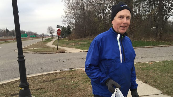 John Robertson, 65, walks every day in Lathrup Village, picking up trash along the way. He's done this for a quarter-century.