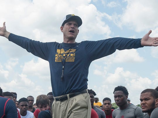 Michigan football coach Jim Harbaugh speaks to participants