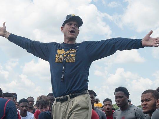 Michigan football coach Jim Harbaugh speaks to participants during a camp June 5, 2015, at Prattville High School in Prattville, Ala.
