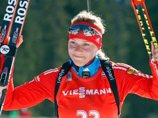 FILE - In this Sunday, March 9, 2014 file photo, Russia's Olga Zaitseva celebrates her third place in the women's 12.5km mass start at the biathlon World Cup competition in Pokljuka, Slovenia. The International Olympic Committee has disqualified three more Russian athletes from the 2014 Sochi Olympics for doping, including one of the country's greatest biathletes, it was reported on Friday, Dec. 1, 2017. (AP Photo/Darko Bandic, File)