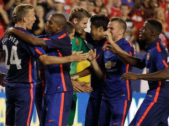 Manchester United's Darren Fletcher (24) celebrates with his teammates after  scoring the winning kick in a penalty kick shootout during  a soccer game at the 2014 Guinness International Champions Cup, Tuesday, July 29, 2014, in Landover, Md. Manchester United won 5-3 in penalty kicks. (AP Photo/Luis M. Alvarez)