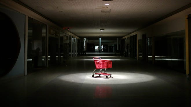 A Target shopping cart rests beneath the center of a still-working spotlight inside Northland Center mall  on Wednesday, Feb. 17, 2016, in Southfield.