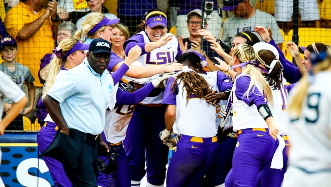 The LSU softball team mobs Bailey Landry after her two-run home run in the Tigers' 8-0 win over Arizona.