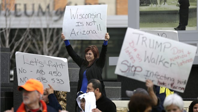 Local Latinos and supporters gather to protest two bills that have been introduced in the state legislature, Monday, March 14, 2016 at Houdini Plaza in Appleton, Wis. Protesters say that bills AB 450 and SB533 are anti-immigrant.