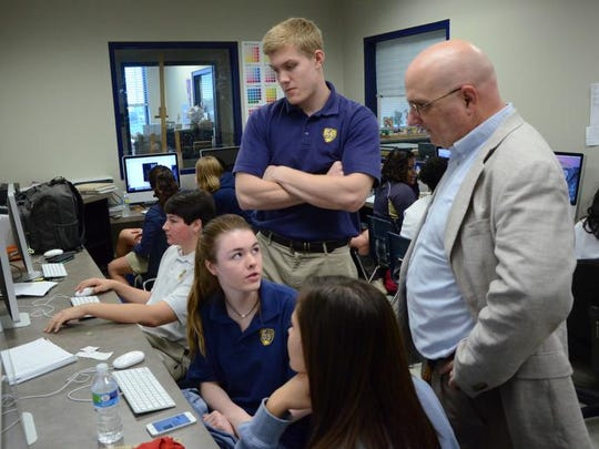In this file photo, journalism instructor Terry Cassreino, right, speaks to former students, clockwise from bottom, Jean-Nicolette Nixon, Frances Huff and Jack Olstad as they work on pages for a school yearbook at St. Joseph Catholic High School.