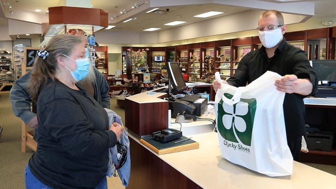 Debi Smith of Akron and her husband, Michael Smith, purchase shoes from Mate Kovacs, assistant manager at Lucky Shoes, on May 7, 2020 in Fairlawn, Ohio. Lucky Shoes has required employees and patrons to wear masks and maintain social distancing.