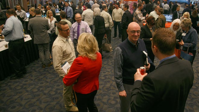 Attendees mingle and network in the Southern Utah Technology Showcase on display in the Garden Room of the Dixie Convention Center during the What's Up Down South Economic Summit Thursday, Jan. 14, 2016 in St. George.