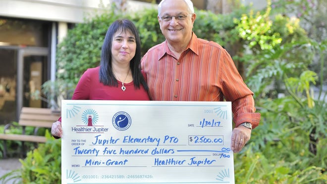Cheri Rosen, representing Jupiter Elementary School PTO, and Gene Hudon, Healthier Jupiter Steering Committee co-chair, pose with the presented check.