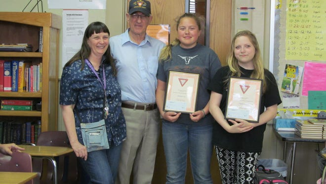 """The 2015-2016 Fleet Reserve Association Americanism/Patriotism essay theme was """"What the United States Flag Stands For.""""  Shown are Julie Hartle, from left, seventh and eighth grade English teacher, FRA Branch 251 President Curtis Grant and Viola Eighth Grade students Bobbielynn Trett, second place and Angelina Valente, first place."""