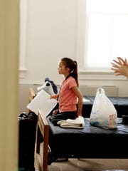 Eight-year-old violinist Jacqueline Rodenbeck of Tucson, Arizona puts her things in her room on arrival day for participants in HeifetzPEG, or Program for the Exceptionally Gifted, on Thursday, July 14, 2016 at Mary Baldwin College. The PEG students, aged 8 to 13, come from all over the country and have to apply and do a video audition before being chosen to be accepted into the three-week stringed instrument program.