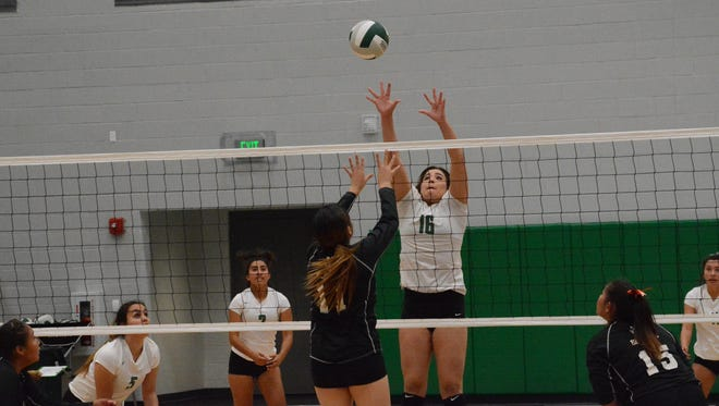 Farmington's Chloe Finch jumps up looking to block a hit by Gallup's Ericka Begay, No. 11 in black, during Thursday's District 1-5A semifinals match at Scorpion Arena.