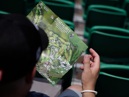 Jason Faylin of Big Stone Gap, Va., looks over a map on the 18th green.