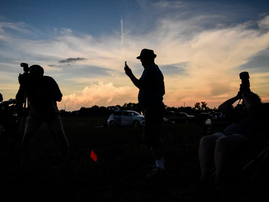 Robert Glynn, David Cull and Laurel Cull take photos and experience the solar eclipse as totality reaches Orchardale Farm in Cerulean, Ky., on Monday, Aug. 21, 2017. The next total solar eclipse visible from North America will be April 8, 2024.
