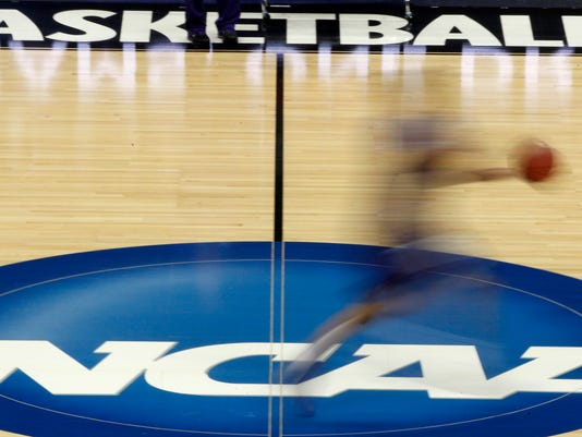 "FILE - In this March 14, 2012, file photo, a player runs across the NCAA logo during practice in Pittsburgh before an NCAA tournament college basketball game. Bank records and other expense reports that are part of a federal probe into college basketball list a wide range of impermissible payments from agents to at least two dozen players or their relatives, according to documents obtained by Yahoo Sports. NCAA president Mark Emmert said in a statement Friday, Feb. 23, 2018, the allegations ""if true, point to systematic failures that must be fixed and fixed now if we want college sports in America."" (AP Photo/Keith Srakocic, File)"