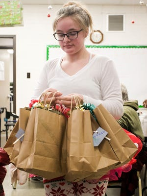 Anne-Marie Wolfe, 12, of Stewartstown, passes out a handful of gift bags to residents at the White Rose Senior Center, during a special Christmas celebration Thursday, Dec. 22, 2016. Asked what she'd like for Christmas, Anne-Marie chose to do something for the people at White Rose Senior Center.  Amanda J. Cain photo