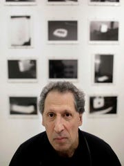 """In this Wednesday, Feb. 22, 2017 photo, photographer Karl Baden, of Cambridge, Mass., sits for a photo in front of an exhibit of his photographs from 1976 called """"Thermographs,"""" at the Miller Yezerski Gallery, in Boston. On Feb. 23, 1987, long before they were called selfies, Baden snapped a simple, black and white photo of himself. Then he repeated it, every day, for the next three decades. Baden's """"Every Day"""" project turns 30 years old Thursday, Feb. 23, 2017."""
