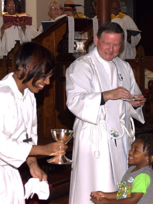 The Rev. Jerry Prickett and chalice bearer Janee Thomas giving communion to young Keyon Thomas at St. Matthias Episcopal Church.