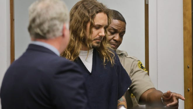 Tim Lambesis, the lead singer for the Metal band As I Lay Dying, is escorted by a San Diego sheriff deputy into Superior Court for his arraignment.