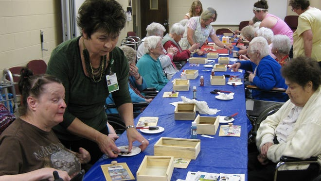 Residents of Aspirus Care & Rehab in Medford paint and decorate memory boxes with the assistance of Aspirus volunteers.