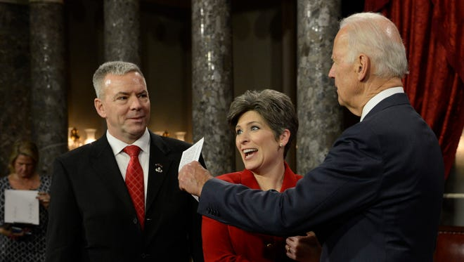 Sen. Joni Ernst, R-Iowa, gets ready to participate in a re-enacted swearing-in ceremony performed by Vice President Joe Biden in the Old Senate Chamber at the U.S. Capitol in Washington Jan. 6, 2015. Senators were officially sworn in on the Senate floor earlier in the day. Joni's husband, Gail Ernst, is at left.