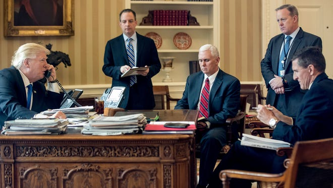 President Donald Trump accompanied by, from second from left, Chief of Staff Reince Priebus, Vice President Mike Pence, White House press secretary Sean Spicer and National Security Adviser Michael Flynn speaks on the phone with Russian President Vladimir Putin in the Oval Office at the White House in Washington. Flynn resigned as President Donald Trump's national security adviser Monday. (AP Photo/Andrew Harnik, File)