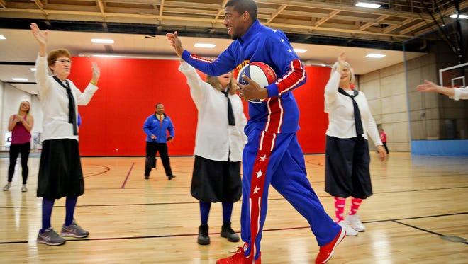 """Harlem Globetrotter Anthony """"Buckets"""" Blakes high fives with granny basketball players at the Downtown YMCA Tuesday, April 14, 2015."""