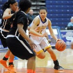 Marian's Samantha Thomas (right) attempts to drive past a pair of Lathrup defenders in Tuesday's Class A regional semifinal game at Southfield High School.