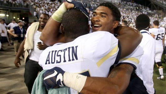 Lance Austin is embraced by teammate and fellow defensive back Shaun Kagawa (44) after his winning blocked kick return Saturday.