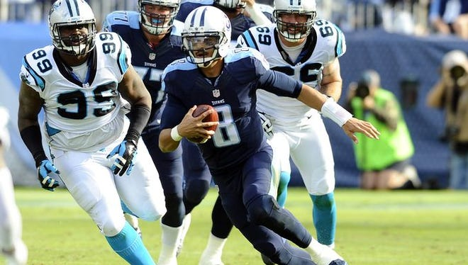 Titans quarterback Marcus Mariota (8) runs for a short gain against Carolina in Sunday's game at Nissan Stadium.