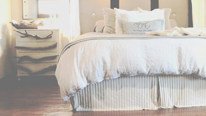 A driftwood dresser with driftwood handles sits in the corner of the bedroom.