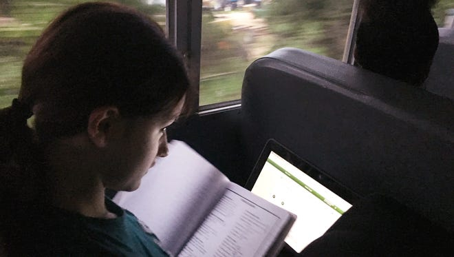 Velvet Engle uses her school-issued laptop computer and textbook to do a geometry assignment while riding a Clarksville-Montgomery County School System bus that Google has equipped with WiFi technology.
