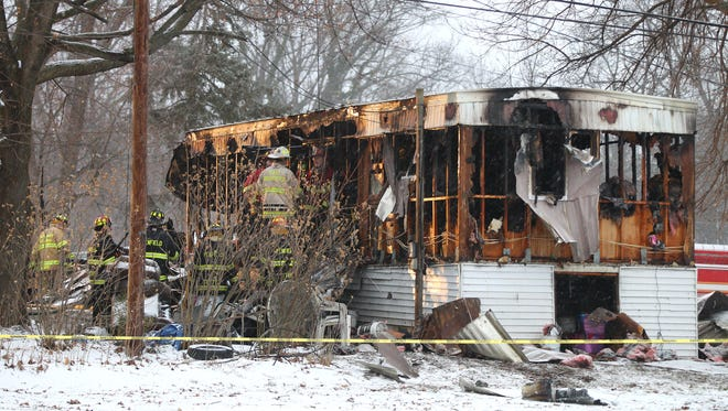 Firefighters investigate a fatal fire in this mobile home in Penfield, N.Y. Three people died in the fire, Louis Beach, Steven Smith and 9-year-old Tyler Doohan.