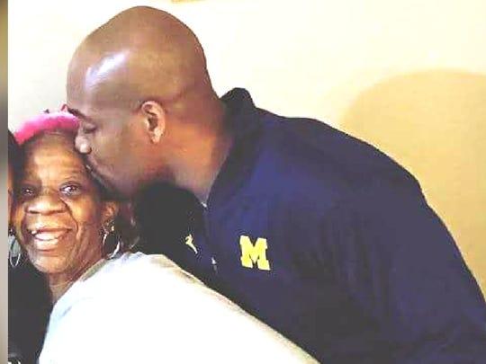 Michigan assistant coach DeAndre Haynes kisses his