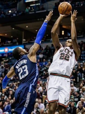 The Bucks' Khris Middleton shoots over the Mavericks' Wesley Matthews on Friday night.