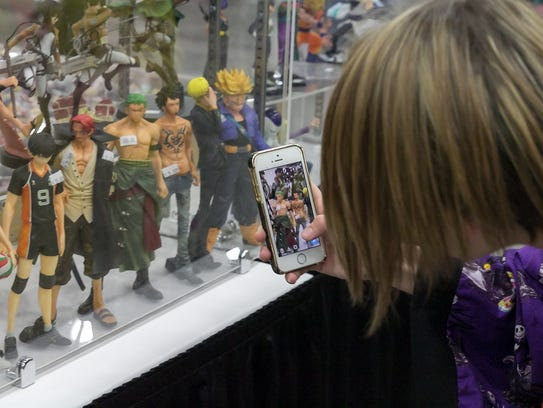 A guest takes a photo of anime inspired action figures