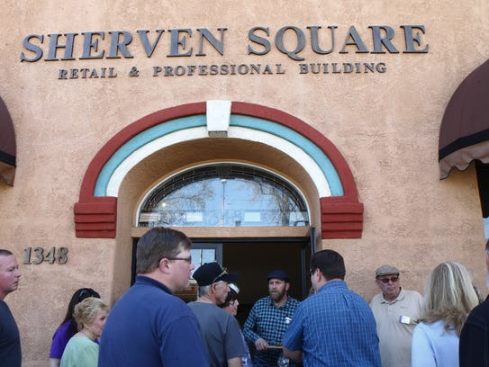 Building owner Nathan Peterson, center, prepares to