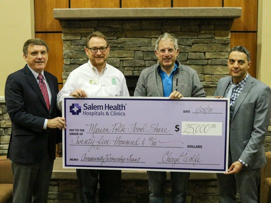 A $25,000 Salem Health Community Partnership Grant is presented to Marion-Polk Food Share. Holding the ceremonial check are, left to right: Bob Wells, Salem Health Board of Trustees; Rick Gaupo, executive director of Marion-Polk Food Share; Alex Beamer, chair of Marion-Polk Food Share Board; and Bahaa Wanly, chief operating officer for Salem Health.