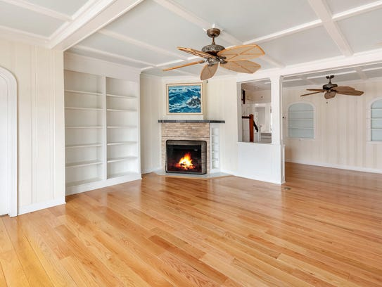 The living room offers coffered ceilings and customized built-ins.
