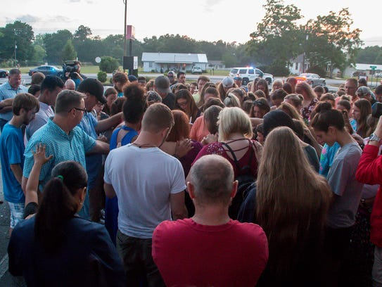 Vigil attendees gather around the Harrell family and
