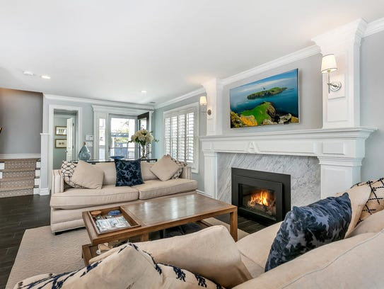 The living room features decorative crown molding and customized fireplace.